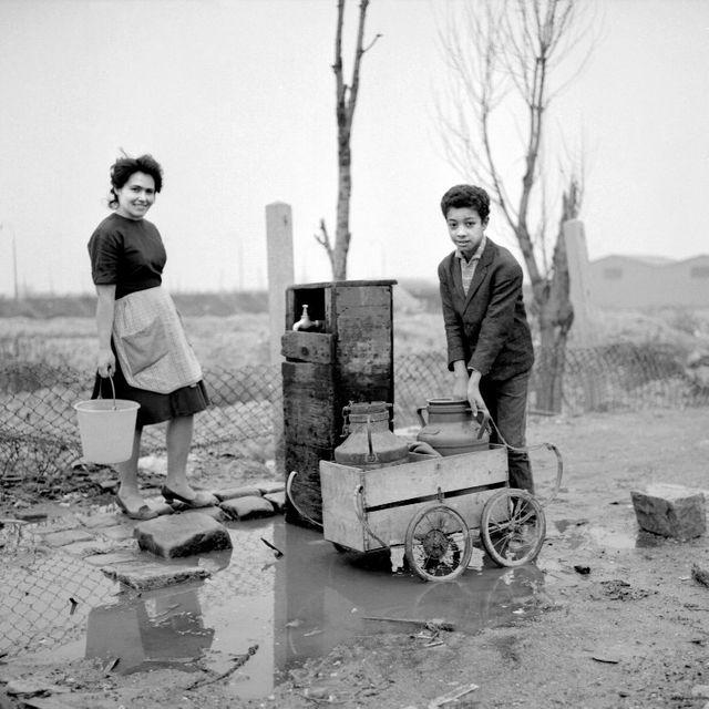 De jeunes gens vont chercher de l'eau à la fontaine au bidonville de Nanterre (1964)