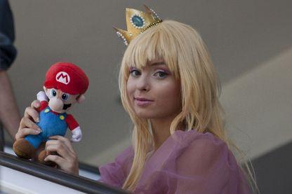 Une cosplayeuse déguisée en princesse Peach, peluche Mario en main