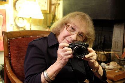Portrait de la photographe Sabine Weiss avec son appareil photo dans son atelier à Paris, France, en 2015.