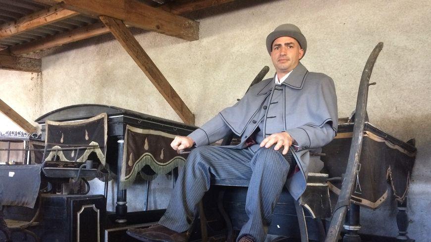 Yvan Quercy fait visiter le musée du corbillard et de l'attelage dans son costume de cocher.