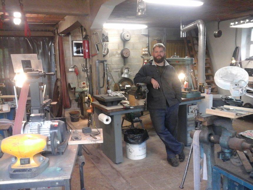 David Brenière, coutelier, dans son atelier divisé en 2 espaces: espace forge (avec fours de forge, pinces, enclumes, marteau-pilon, ...) et espace mécanique (perceuses à colonne, machines abrasives, tourets de polissage, ...)