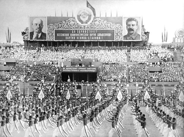 Les gymnastes soviétiques portant des drapeaux avec le marteau et la faucille défilent sous les portraits de Lénine et de Staline à l'occasion de la fête des Sports à Moscou au mois d'août 1946.