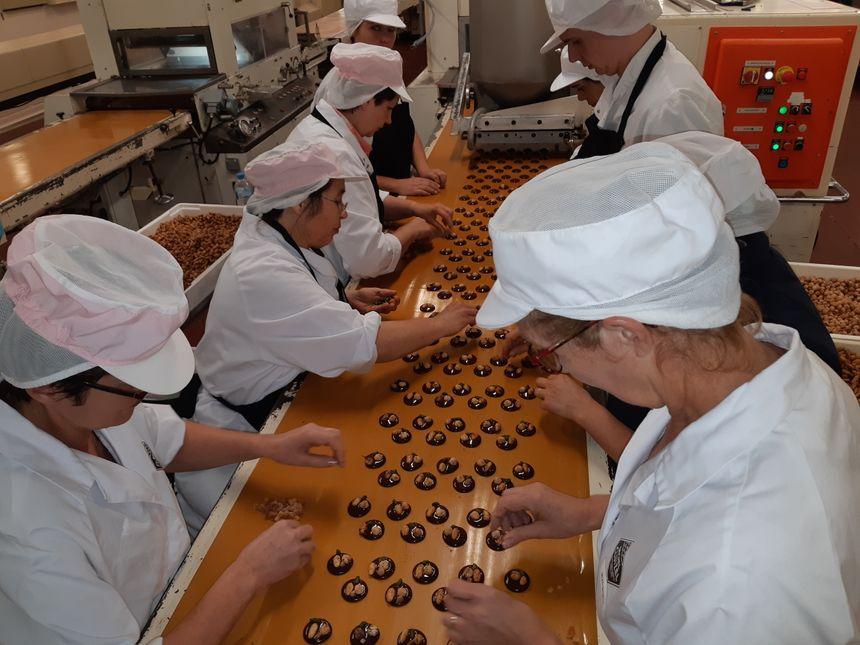 Les fruits, amandes, noisettes ou dés d'orange, qui agrémentent les mendiants sont posés à la main, sous l'oeil vigilant de Sonia