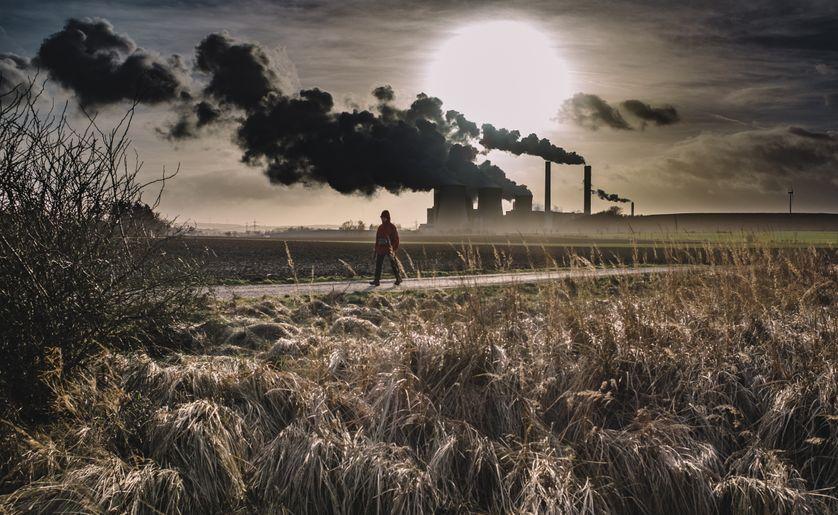 Silhouette d'une personne marchant  près d'une usine
