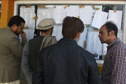 Des observateurs afghans vérifient les résultats des votes affichés dans un centre de vote après le dépouillement du scrutin aux élections législatives du pays à Kaboul le 22 octobre 2018