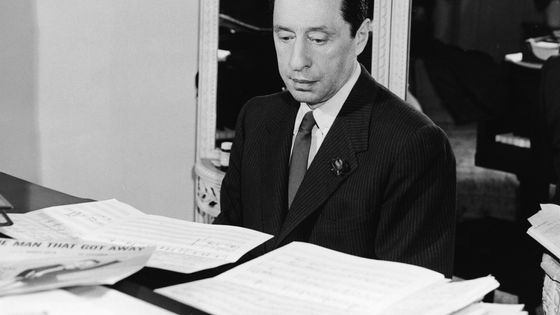 American composer Harold Arlen (1905 - 1986) works on a composition on a piano, 1965. The songbook for 'The Man That Got Away,' which he and lyricist Ira Gershwin wrote for the film 'A Star Is Born,' rests among sheet music on top of the piano