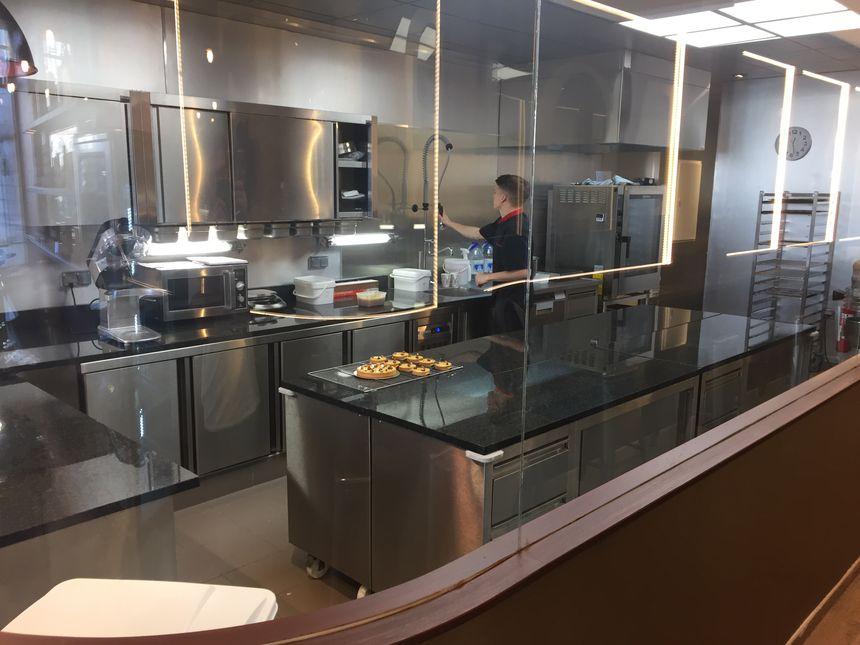 À l'intérieur de cette cuisine entièrement vitrée, Romain Cabaret prépare des tartelettes.