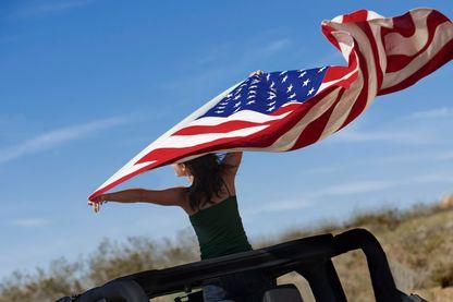 Femme dans le désert avec le drapeau américain comme étendard.