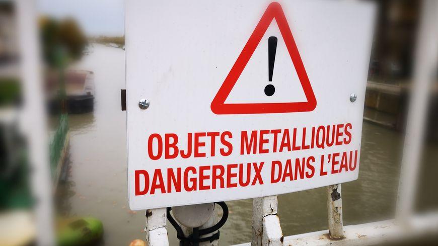 Un panneau installé sur le pont,  qui enjambe le Canal du Midi, prévient de la dangerosité du site