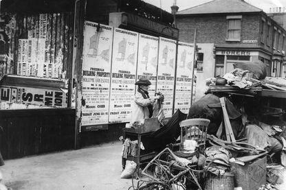 Une femme âgée, expulsée de son logement et occupée à récupérer et à trier ses affaires dans la rue... en 1913.