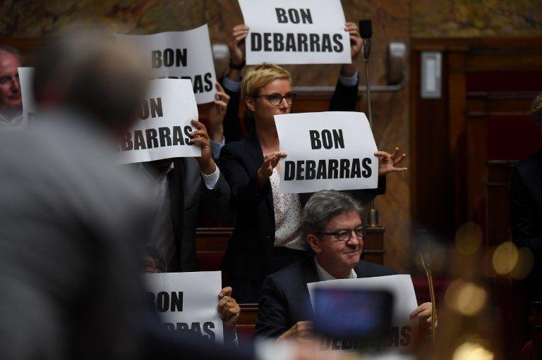 """Les députés de la France insoumise brandissent des pancartes """"bon débarras"""" au moment où Manuel Valls prend la parole pour la dernière fois à l'Assemblée nationale."""
