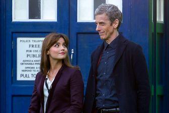Jenna Coleman (Clara Oswald) et Peter Capaldi (le 12ème Docteur), devant le TARDIS (machine à voyager dans le temps et l'espace), sur le tournage de la huitième saison de Doctor Who (mars 2014, Cardiff, pays de Galles)