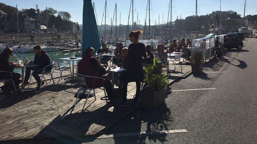 Sur le bord du port de Saint-Valery en Caux, les touristes profitent des derniers jours de beau temps pour manger en terrasse.