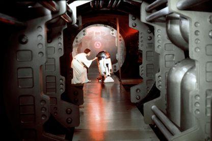 """Carrie Fisher (princesse Leia) et Kenny Baker (R2-D2), sur le tournage de """"Star Wars, épisode IV : Un nouvel espoir"""", réalisé par George Lucas (1977)"""