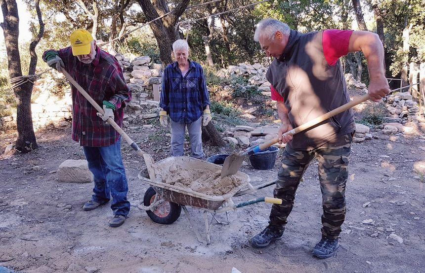 Bénévoles avec Inge, au centre, malaxant le mortier à l'ancienne.