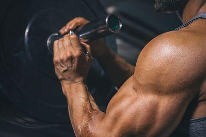 Gros plan d'un bodybuilder préparant une barre dans une salle de sport