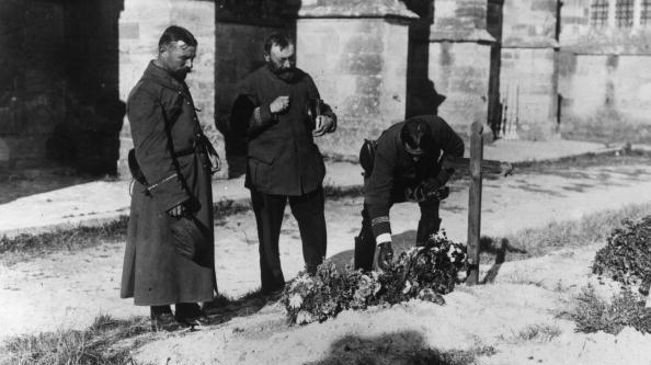 Des officiers visitent une tombe recouverte de fleurs en France pendant la Première Guerre mondiale.