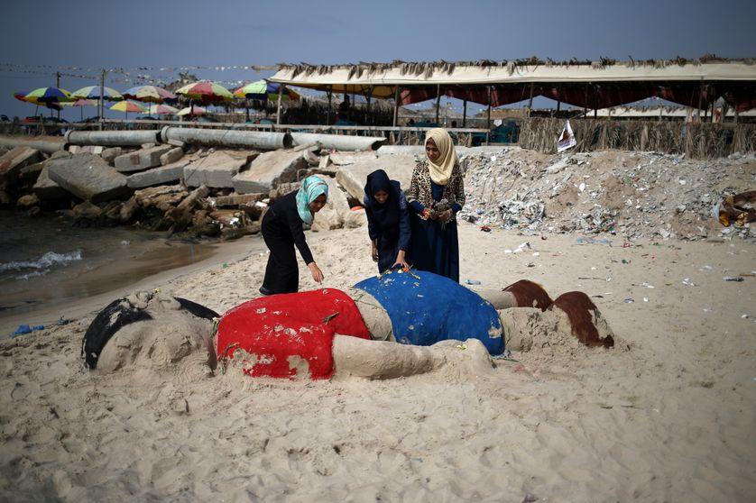 De jeunes Palestiniennes déposent des fleurs sur une sculpture représentant le corps d'Aylan, sur une plage de Gaza.