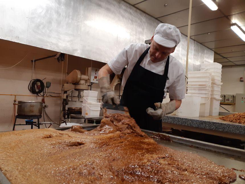 Alain travaille à la spatule la nougatine pour en faire des boudins qui seront ensuite passés dans une sorte de laminoir
