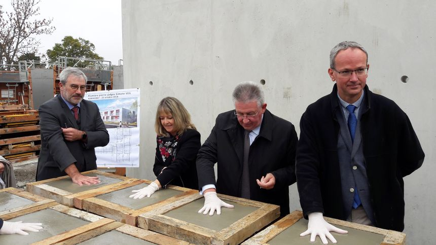 Les représentants de l'OPHIS, le président du Conseil départemental du Puy-de-Dôme, le maire de Romagnat posent leurs empreintes sur le chantier de la résidence