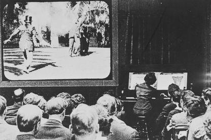 Une séance de cinéma (muet) en 1913, avec une musicienne accompagnant le film au piano