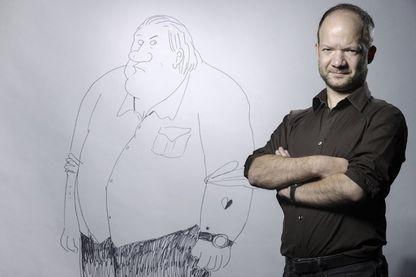 Auteur et dessinateur de bande dessinée, Mathieu Sapin pose à côté de l'un de ses dessins de Gérard Depardieu (Paris, 12 janvier 2017)