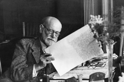 Sigmund Freud, neurologue autrichien, fondateur de la psychanalyse, dans son bureau de Vienne, lisant un manuscrit.