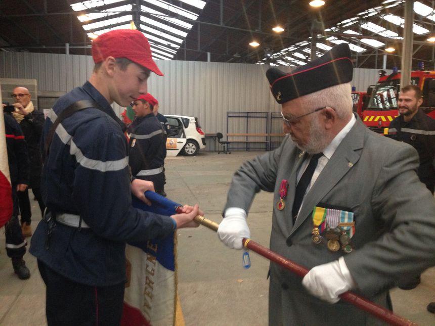 Clément, 14 ans, aidé d'un retraité militaire, pour fixer le drapeau sur la hampe en bois