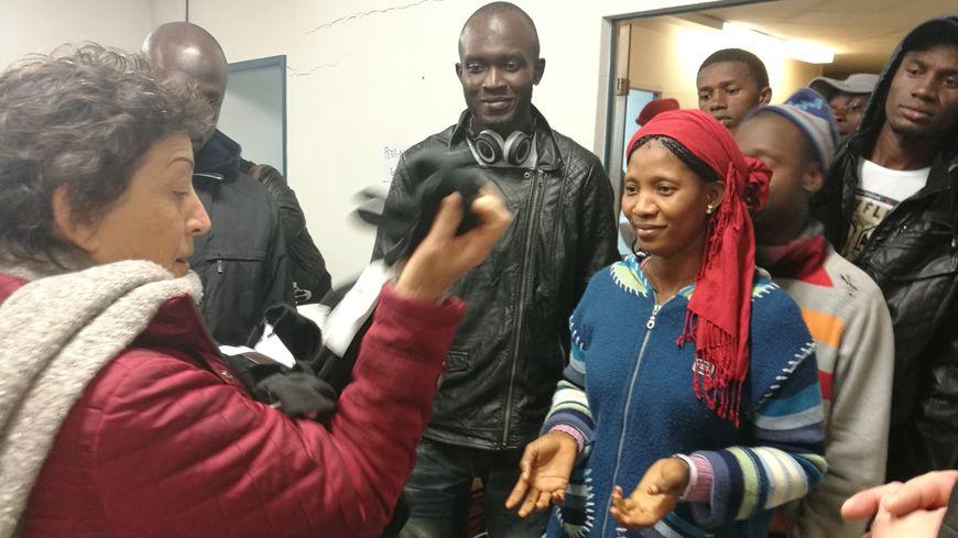 Une bénévole offre une dizaine de paires de gants et de bonnets