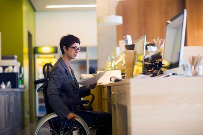 Femme en fauteuil roulant, au travail dans un bureau