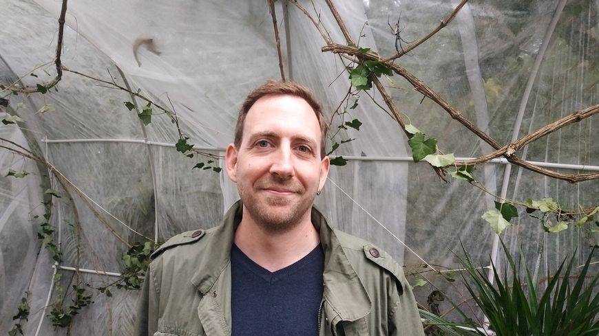 Olivier Marquis, gestionnaire de la collection reptiles, amphibiens et invertébrés au Parc zoologique de Paris (et une araignée néphile derrière lui !)