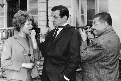 La jeune actrice Sabine Singen et Lino Ventura sur la gauche, alors que Francis Blanche vise de son pistolet la jeune fille, sur le tournage des Tontons flingueurs en 1963.