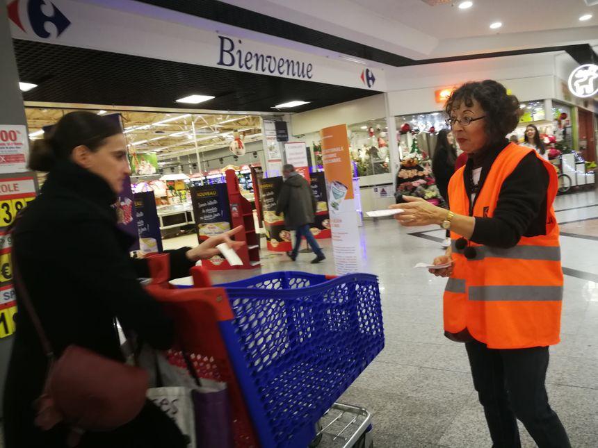 Guilaine distribue des tracts pour inciter les clients à ne pas oublier la Banque Alimentaire à la sortie des caisses