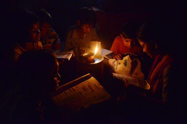 Des écoliers indiens du Pendjab lisent à la lumière d'une bougie faute d'accès à l'électricité.