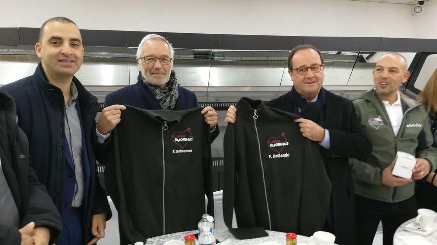 """François Hollande a visité l'épicerie sociale et solidaire """"Le Coeur Dijonnais"""". A l'issue de cette visite il s'est aux côtés de François Rebsamen il s'est vu remettre un sweat-shirt portant son nom."""