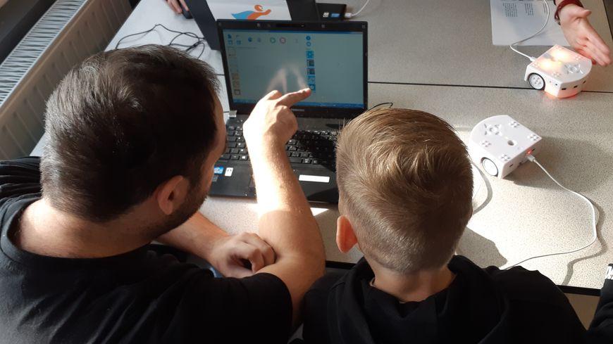 """Chaque élève a bénéficié de l'aide d'un """"coach"""" pour apprendre à programmer le petit robot situé à droite de la table."""