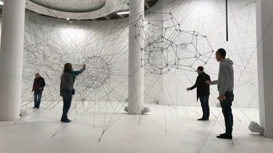 Des visiteurs jouent de la musique avec les fils de la toile d'araignée géante de l'oeuvre Algo-R(h)i(y)thms de l'artiste argentin Tomas Saraceno. Paris, Palais de Tokyo.