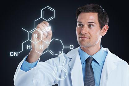 Prise de vue studio d'un scientifique dessinant des structures moléculaires sur une surface transparente