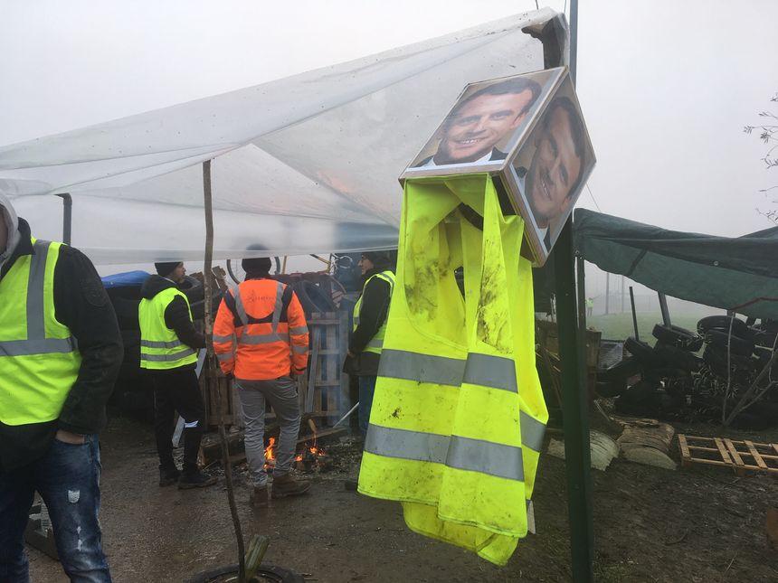 Plus de 50 militants tiennent un campement où s'entrechoquent palettes, pneus et photos d'Emmanuel Macron à Albens en Savoie.