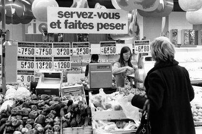 Clients faisant leurs courses au rayon des légumes d'un supermarche en 1980