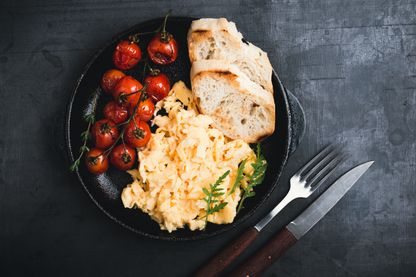 Plat d'oeufs brouillés, au pain grillé e taux tomates cerises.