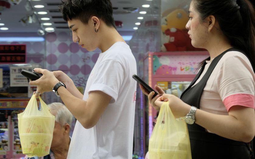 Deux personnes regardant leur smartphone à Taipei, le 24 octobre 2018.