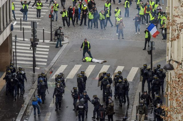 Un homme gît sur le sol près de la police anti-émeute sur l'avenue des Champs-Élysées à Paris le 8 décembre 2018