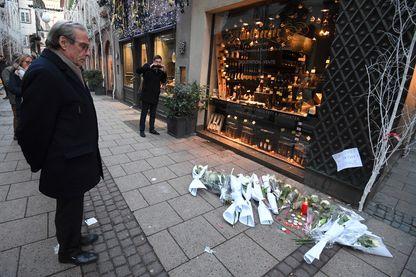 Roland Ries devant des bouquets de fleurs déposées dans la rue en hommage aux victimes de la fusillade mortelle à Strasbourg, le 12 décembre 2018.