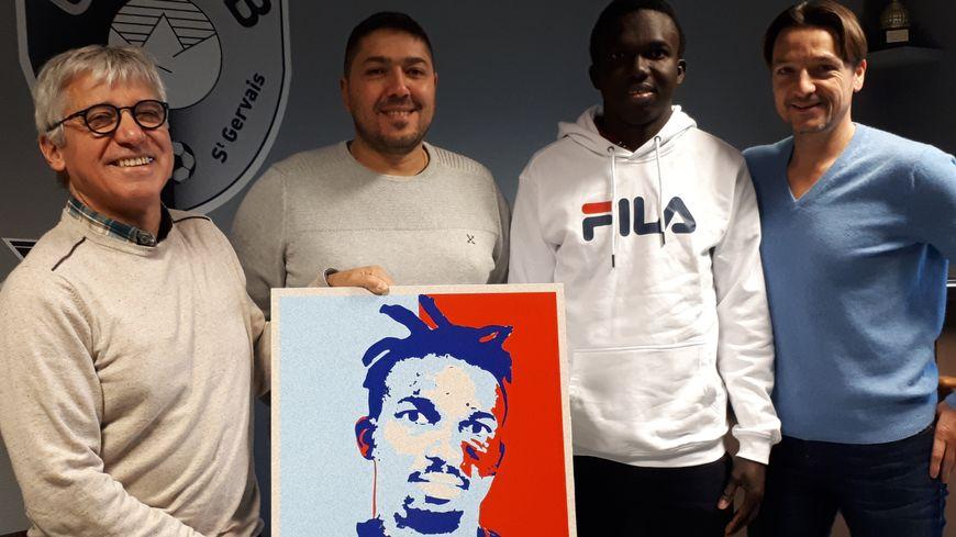 Souleymane Diallo entouré, de gauche à droite, de Jacky Périllat de sa famille d'accueil, Aziz Harraguia, son employeur, et Marc Bervas son entraîneur de foot