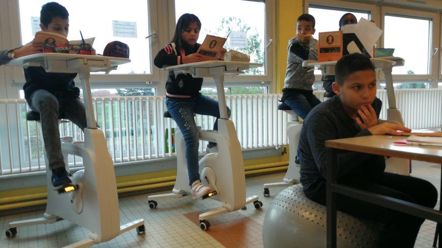 Les vélos bureaux de l'école Anne Frank de Chalon-sur-Saône. Ayoub, lui, est assis sur un gros ballon de gym.