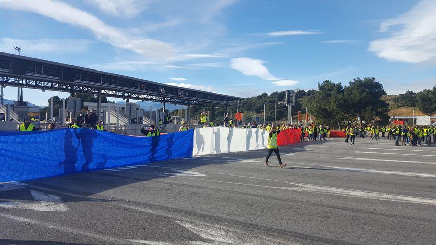 Un immense drapeau français déployé par les Gilets jaunes devant le péage