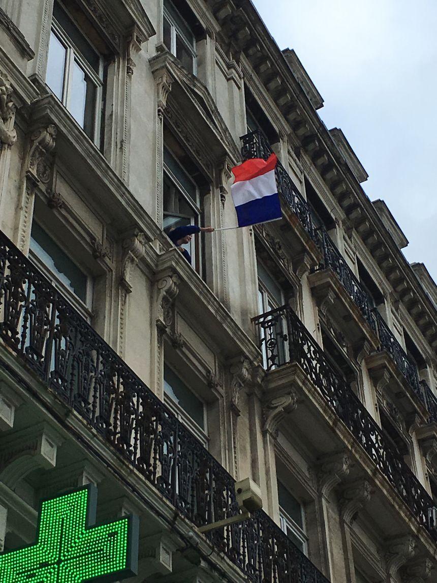 Au passage des manifestants, des drapeaux tricolores aux fenêtres