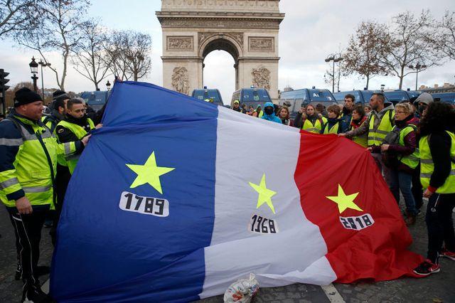 1789, 1968, 2018 : les manifestants brandissent un drapeau français devant l'Arc de Triomphe samedi 8 décembre 2018