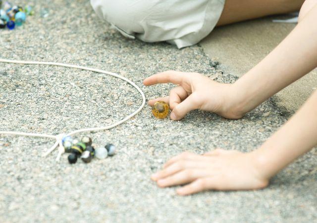 Les enfants jouent aux billes à l'école depuis des générations.